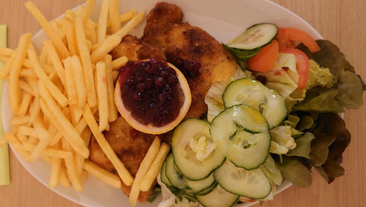 Schweineschnitzel paniert mit Pommes Frites, Salat und Preiselbeeren
